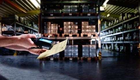 Industriefotografie---Handscaner-liest-Lagerschein-in-Lagerhalle-mit-Regalen