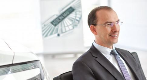Corporate/Firmenprofil - Mann mit Brille+Anzug+Krawatte, sitzend_Aston Martin