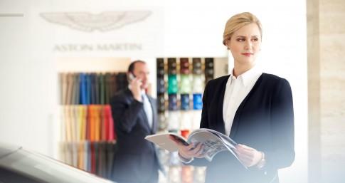 Corporate/Firmenprofil - Frau mit Businesskleidung liest in Katalog_Showroom Aston Martin