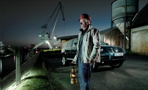 Peoplefotografie---Alter-Hafenarbeiter-rotem-Arbeitshelm-haelt-eine-Petroleumlampe--naechtliche-Stimmung--Hafen-Neuss