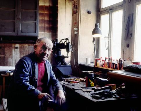 Peoplefotografie---Alter-Schuhmachermeister-sitzt-rauchend-in-seiner-Werkstatt-und-blickt-zufrieden-in-die-Kamera