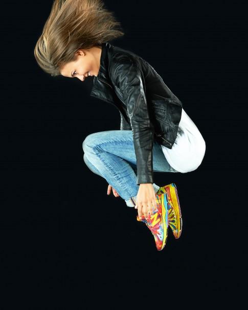 Peoplefotografie---Junge-Frau-mit-bunten-NewBalance-blauer-Jeans-weissem-T-Shirt-schwarzer-Lederjacke-springt-durch-die-Luft-nach-unten