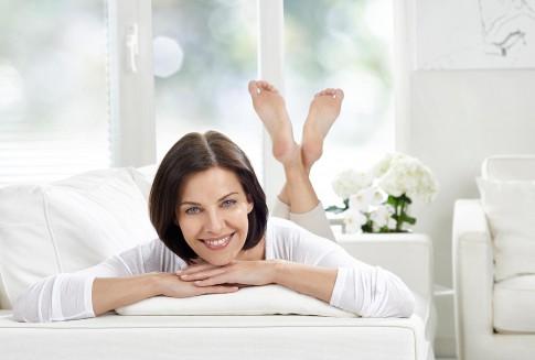 Peopleaufnahme -laechelnde Frau auf Sofa in weissem Ambiente