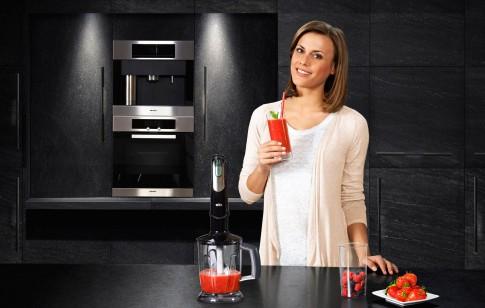 Peoplefotografie--Frau-in-schwarzem-Kuechenambiente-bereitet-einen-ErdbeerSmoothie--Braun-Multiquick-Kampagne