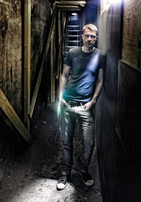 Peoplefotografie---Mann-mit-T-Shirt-steht-in-einem-Kellerflur-blickt-in-die-Kamera
