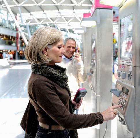 Peoplefotografie--Best-Ager-Frau-tippt-eine-Nummer-am-Muenztelefon-ein--Telekom-Airport-Duesseldorf