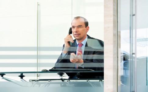 Corporate/Firmenprofil - Mann im Anzug telefoniert am Schreibtisch_Aston Martin
