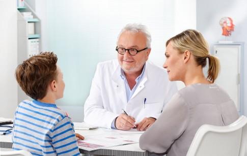 Arztgespraech   -   Mutter und Kind unterhalten sich mit Arzt in dessen Sprechzimmer