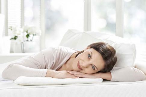 Peopleaufnahme  -  Frau entspannt auf Sofa in weissem Ambiente