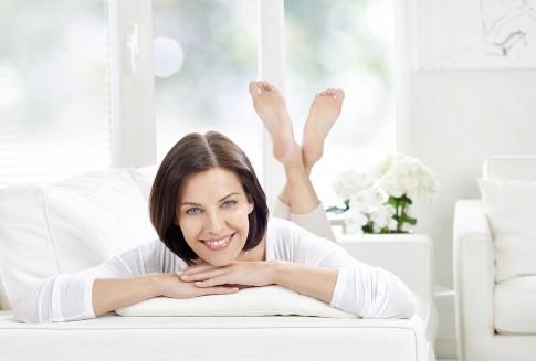 Peopleaufnahme  -  laechelnde Frau auf Sofa in weissem Ambiente