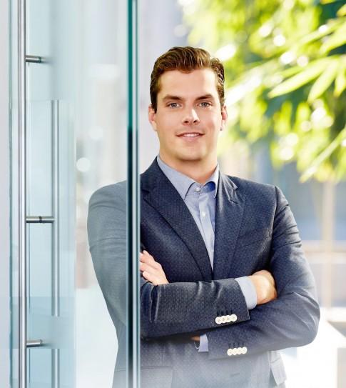 Firmenportraits---Junger-Mann-mit-Jacket-steht-an-einem-Glaseingang