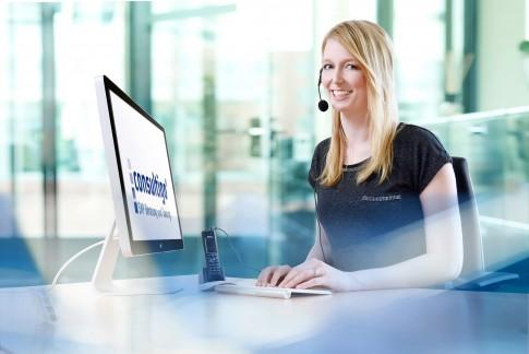 Firmenportraits----Junge-Dame-mit-Headset-im-Buero-am-Computer