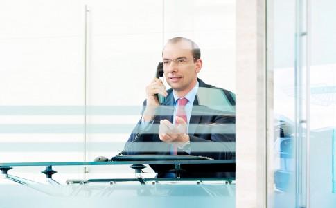 Firmenportraits---Mann-mit-Businesskleidung-telefoniert-am-Schreibtisch