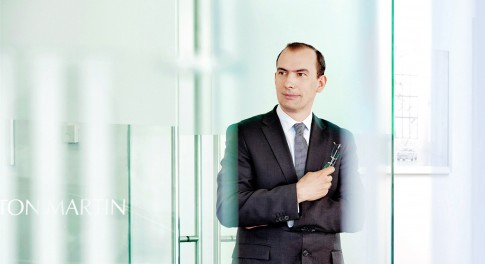 Firmenportraits---Mann-mit-Anzug-und-Krawatte-zwischen-Glastueren--AstonMartin-Showroom