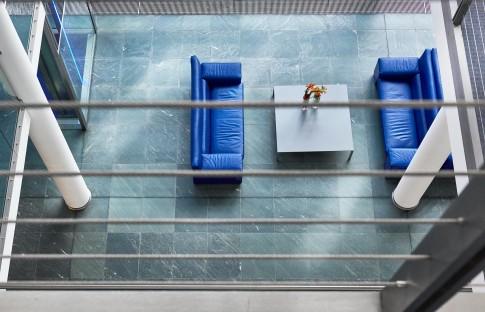 Architektur--Blick-von-oben-auf-blaue-Sofas-auf-mintgruenem-Steinboden--Bankgebaeude