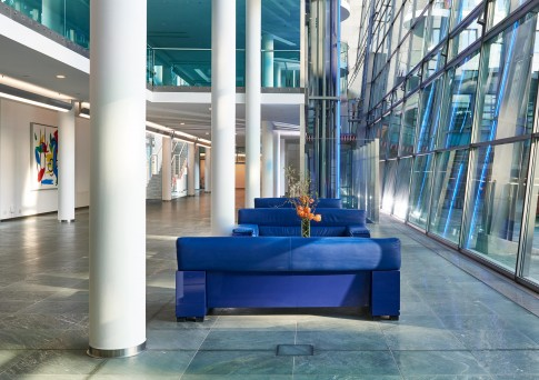 Architektur--Eingangshalle-eines-Bankgebaeudes-mit-blauen-Sofas-und-weissen-Saeulen