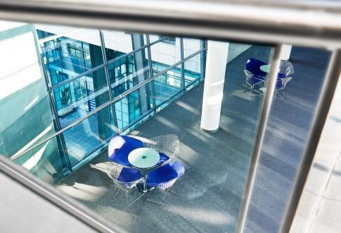 Architektur--Blick-von-oben-auf-kleine-Designertische-und-Stuehle---Bankgebaeude-mit-blaugruenen-Fenstern