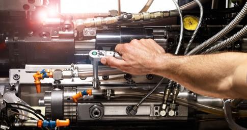 Industriefotografie---Hand-mit-Nussschluessel-zieht-Schraube-fest---Wartung-einer-Maschine