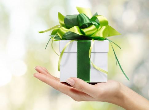 Weisses Geschenkpaeckchen mit grünen Schleifen auf ausgestreckter Hand