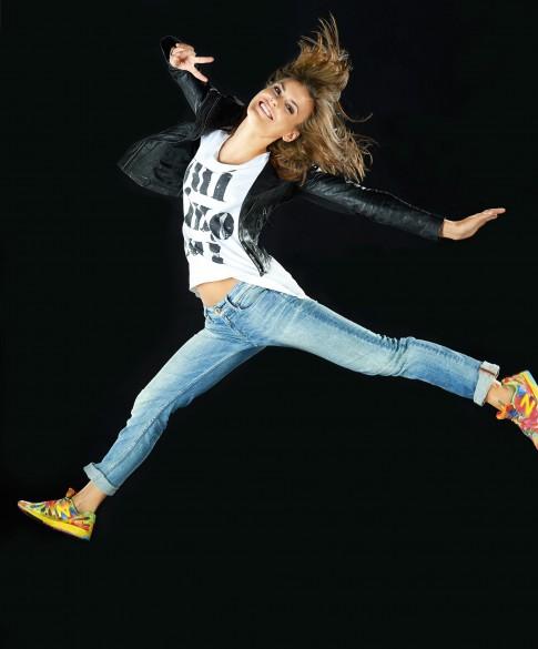 Peoplefotografie---Junge-Frau-mit-bunten-NewBalance-blauer-Jeans-weissem-T-Shirt-schwarzer-Lederjacke-springt-durch-die-Luft-und-lacht