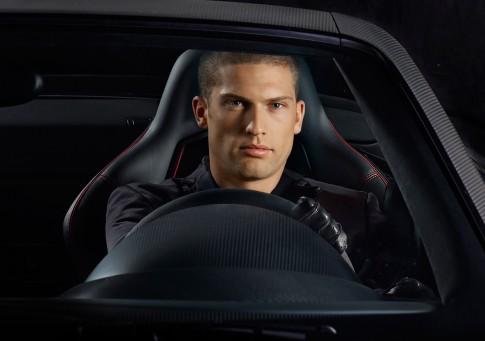 Peoplefotografie---Mann-am-Steuer-eines-Audi-R8GT-schwarze-Ausstattung-blickt-frontal-in-die-Kamera