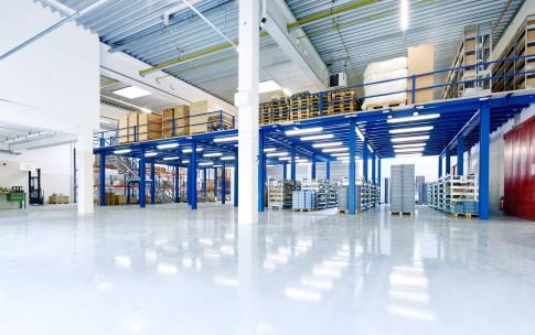 Industriefotografie---Industrielagerhalle-in-blau-weisser-Farbe-und-glaenzendem-Boden