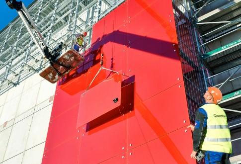 Industriefotografie---GlasPanel-Montage---rote-GebeaudeFassade