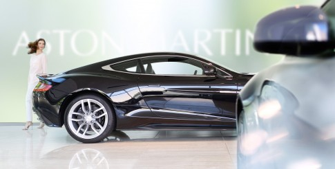 Firmenportraits---Dame-betrachtet-Auto-im-Aston-Martin-Showroom
