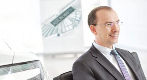 Firmenportraits---Mann-mit-Brille-Anzug-und-Krawatte-sitzend-im-Autosalon--Aston Martin
