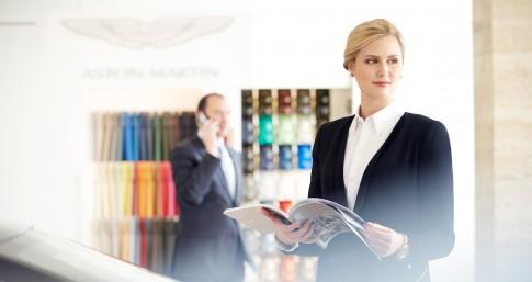 Firmenportraits---Dame-in-Businesskleidung-blaettert-in-einem-Katalog--Showroom Aston Martin