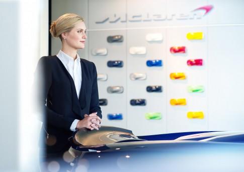 Firmenportraits---Dame-in-Businesskleidung-betrachtet-einen-McLaren-im-Showroom